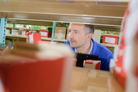 storeroom: View from shelf of man selecting product