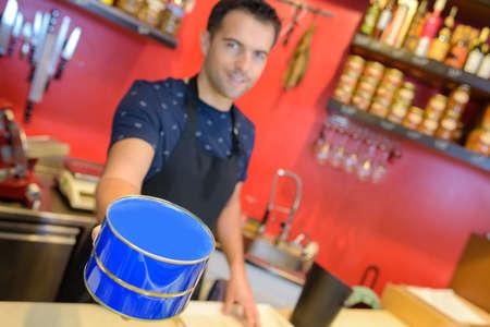 Man in deli holding blue tin Stock Photo