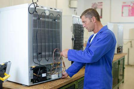 Repairman working on fridge