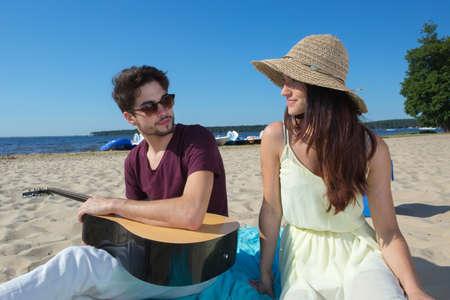 peer to peer: hombre joven con su guitarra y su novia en la playa
