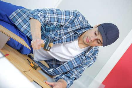 wood flooring: repair building and home concept - male measuring wood flooring
