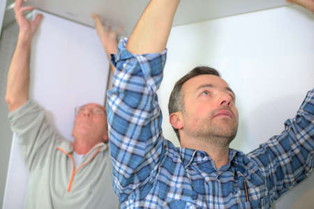 plasterboard: Men fitting plasterboard to ceiling Stock Photo