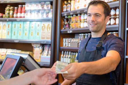Cashier handing notes to customer