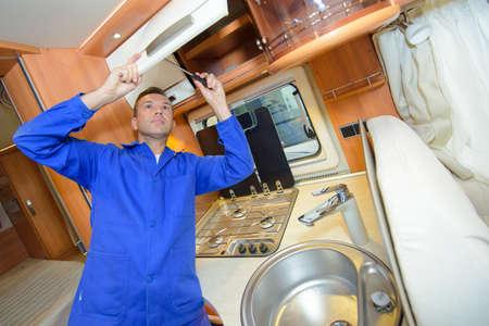 maintenance fitter: Mechanic working on interior of camper van