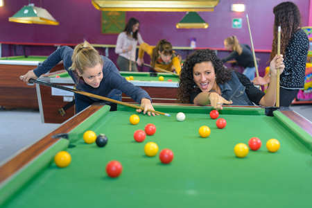 pool hall: Two women playing pool Stock Photo