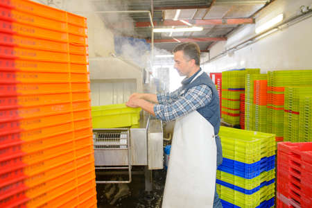 operative: Man in factory washing plastic crates