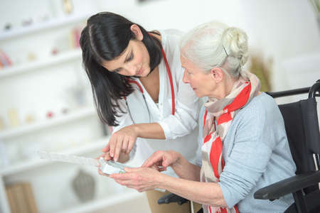 Talking old lady through her medication Stock Photo