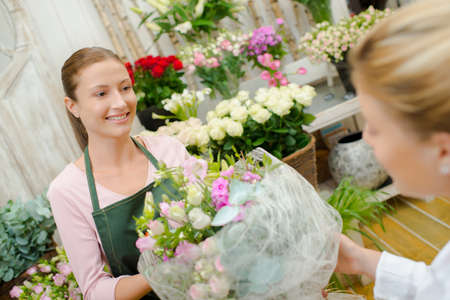giftwrapped: Florist giving arrangement of flowers to customer Stock Photo