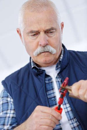 senior handyman trying to fix something Stock Photo