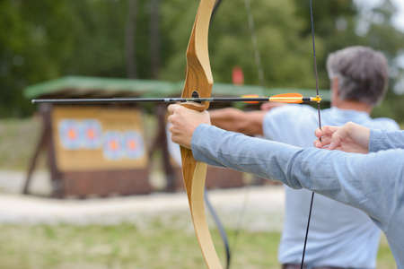 Man and woman practicing archery