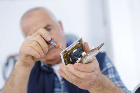 dismantle: man using screwdriver on broken cell phone