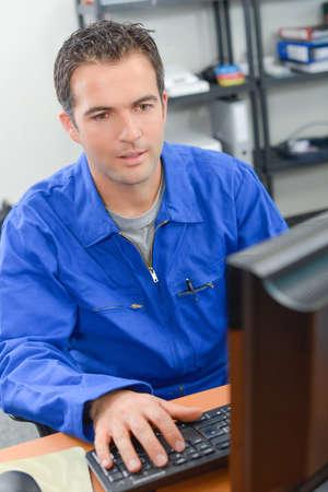 overol: El hombre con un mono azul sentado en su escritorio