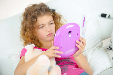 sulk: Girl looking at a digital tablet Stock Photo
