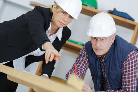 instructs: construction manager instructs a subordinate in the workplace