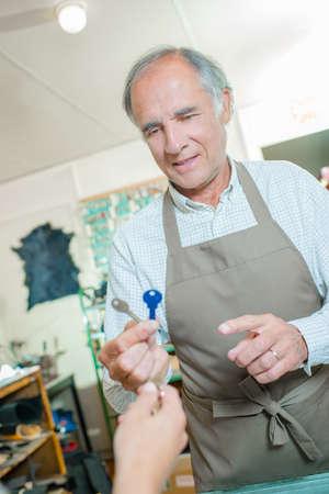 cobbler: Cobbler holding two keys Stock Photo