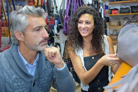 shop keeper: Shop keeper showing handbags to customer
