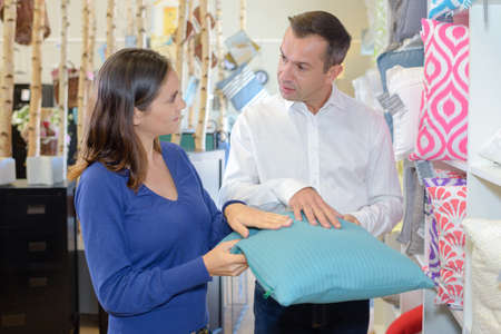 bedlinen: young man and woman buying bedding in supermarket