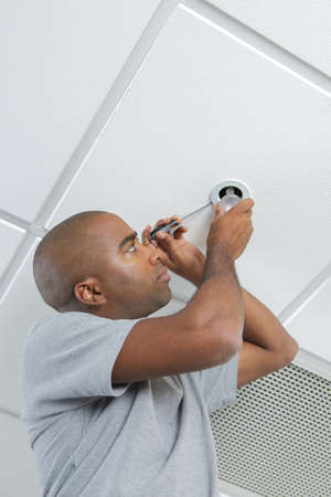 fitting in: Man fitting spotlight in ceiling