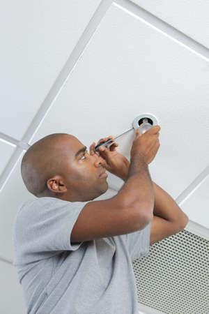 fitter: Man fitting spotlight in ceiling