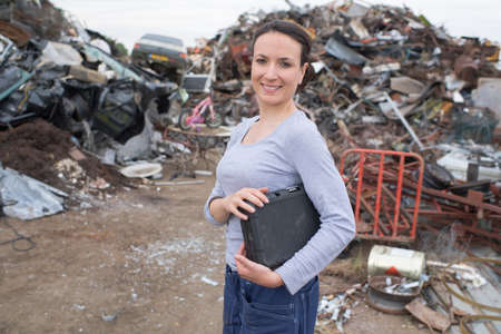 junkyard: young female manager at dumpsite Stock Photo