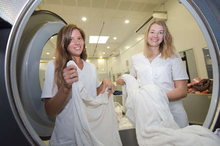 employees of dry cleaning loads a professional washing machine Reklamní fotografie