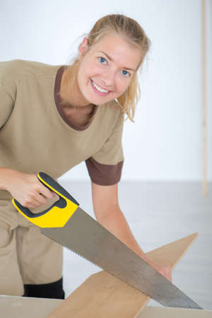 woman sawing wood smiling portrait