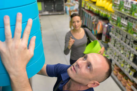 supermarket series: sales assistant helping a female client reaching item