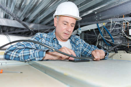 mature electrician fixing wiring in the ceiling Stock Photo