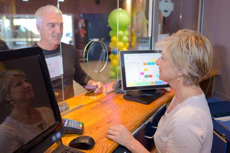 banker at her desk counter attending a customer Standard-Bild