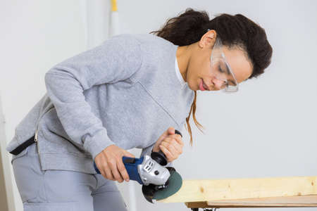 cabinetry: young adult female worker grinding plank with electric grinder