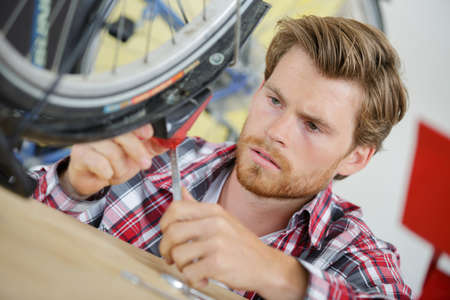 contended: professional repairer fixing bike Stock Photo