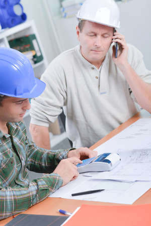 Two men at desk with calculator, phone and plans Stock Photo