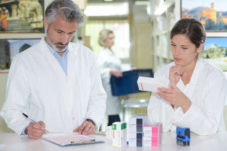 medicine box: pharmacists standing at counter and showing medicine box in pharmacy
