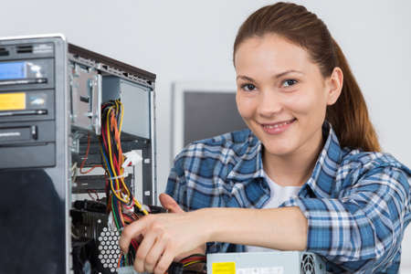 portrait of a female technician fixing computer with her colleague Stock Photo