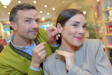 female trying earrings in retail store