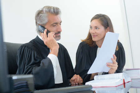 sitting at desk: Legal worker using telephone