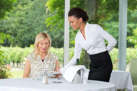 Waitress serving lady in restaurant Stock Photo
