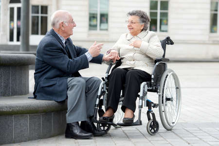 happy senior: old couple a man and woman sitting in wheelchair outdoors