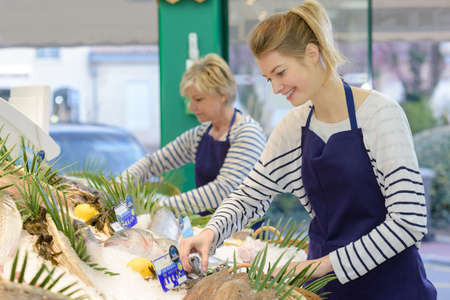 fish shop: women fishmongers smiling and tidying display Stock Photo
