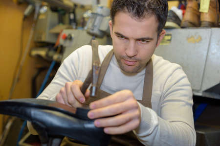 shoe cobbler repairing heel on a pair of shoes Stock Photo