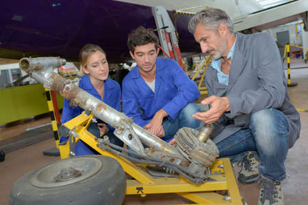 dismantled: Students inspecting aircraft landing gear
