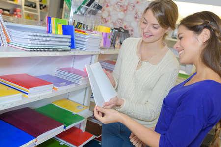 papeleria: Las mujeres que buscan en los libros en la tienda de artículos de papelería