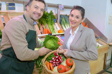 retailer: Portrait of retailer and customer holding basket of fresh vegetables