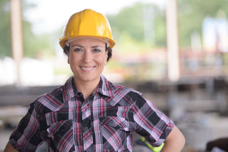 coverall: smily female worker wearing a yellow helmet