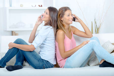 blonde teenager: two friends on a sofa using their mobile phone