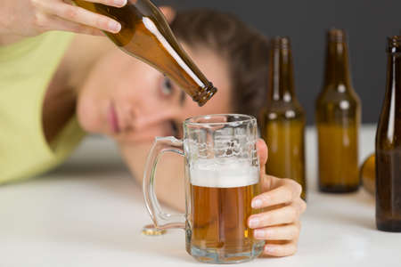 woman pouring a beer out of a bottle
