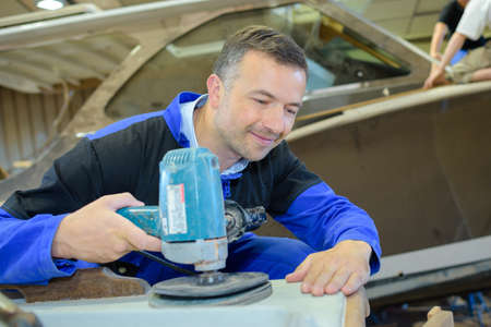 sander: Boatmaker using sander Stock Photo