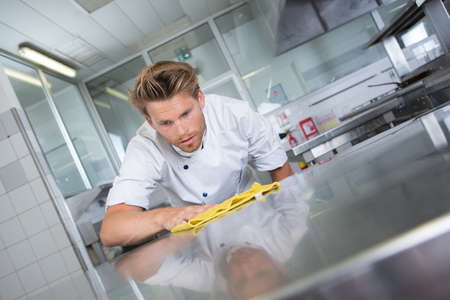 food drink industry: kitchen chef cleaning the restaurants kitchen