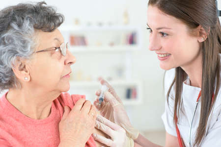 doctor inject influenza vaccine into old woman patient Zdjęcie Seryjne