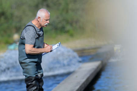 old worker at a fish farm writing down data